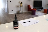 A pump pack of hand sanitiser sits on a benchtop inside the living area of a house.