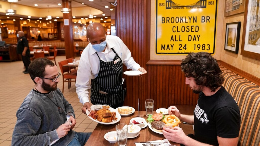 Waiter wearing a mask serves lunch to two men at Junior's Restaurant in New York.
