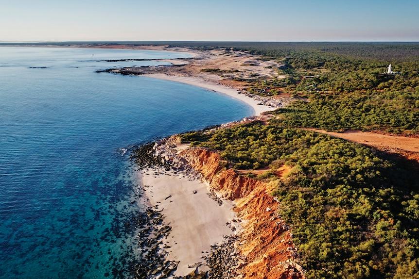Image of the coastline that shows bright blue sea, white beaches and dense green bushland.