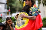 A man hugs a woman who is wearing an Aboriginal flag over her shoulders.