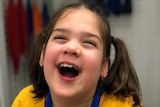 Young girl with brown hair laughs.