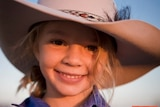 A young girl with a large Akubra hat with text across it saying #stopbullyingnow