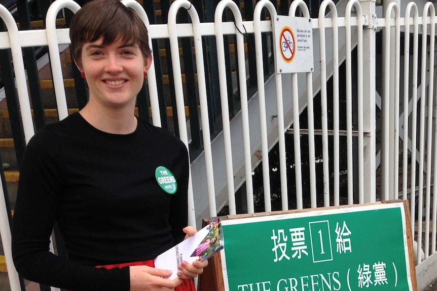 A woman stands next to a Greens sign.