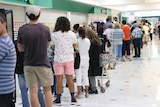 A long line of shoppers queues outside a Woolworths store inside a shopping centre.
