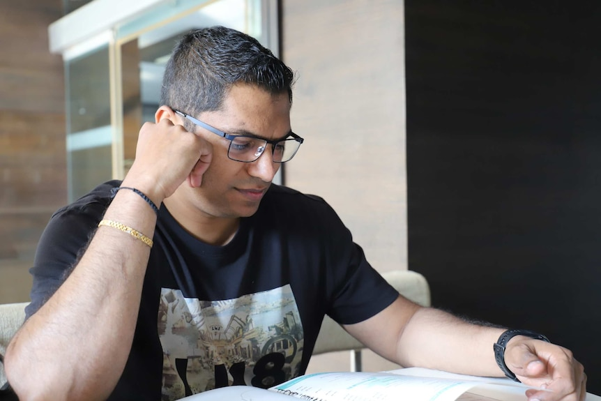 A man in glasses sitting at a desk reading a pamphlet.