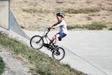 boy riding a bike up a hill