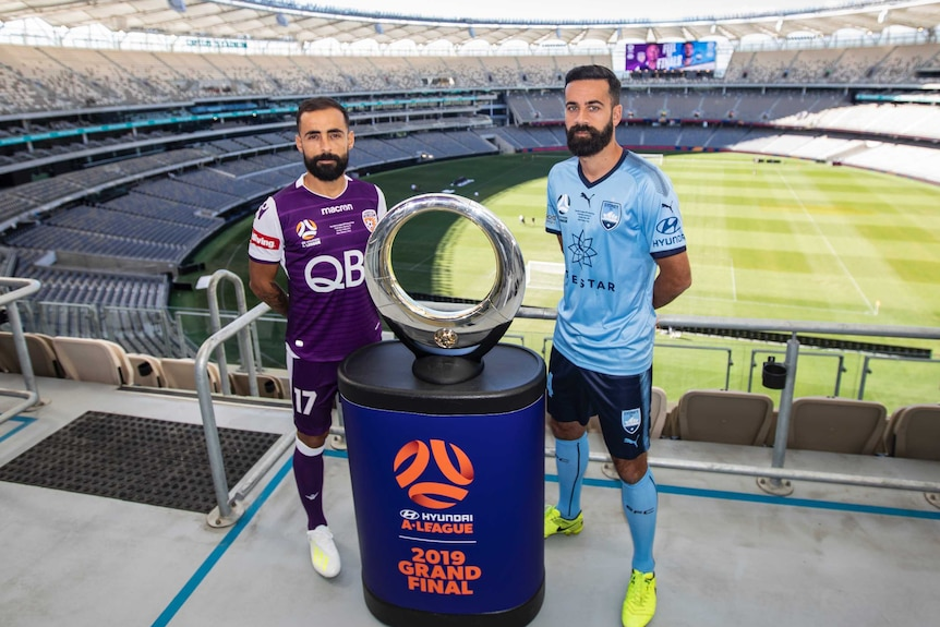 Diego Castro and Alex Brosque stand either side of the A-League trophy. In the background is the expanses of Perth Stadium.
