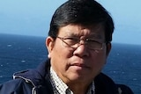 A picture of an older man of Vietnamese heritage with black hair and glasses standing on a boat with the sea in the background.