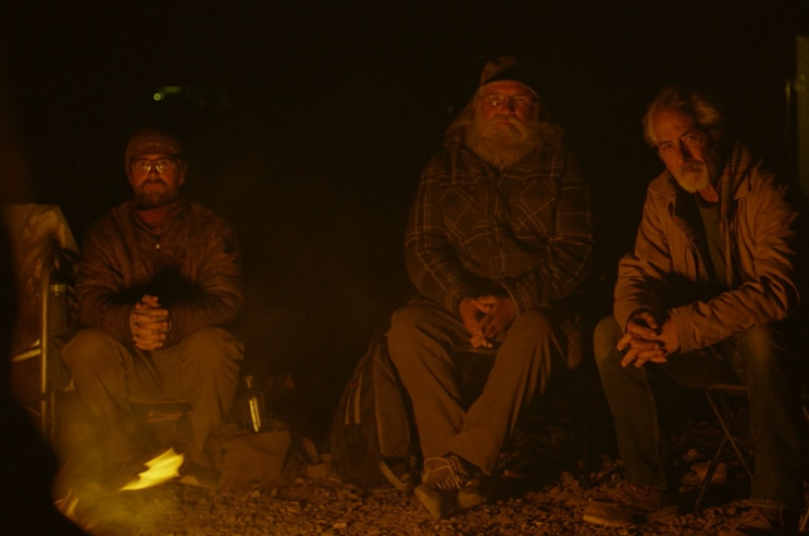 Three men sit on chairs in facing a camp fire, with darkness around them.