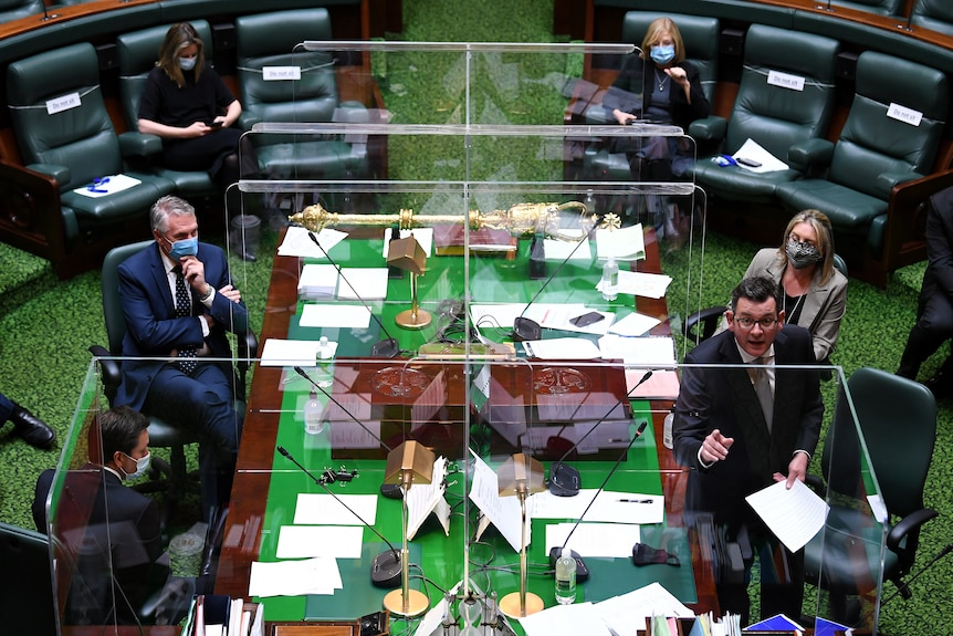 Daniel Andrews speaks in Victorian Parliament behind plastic COVID screen as other MPs watch.