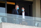 Two members of the World Health Organization team chat on a hotel room balcony in Wuhan.
