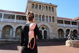 A woman stands outside the Perth Mint with a bra flung over her shoulder.