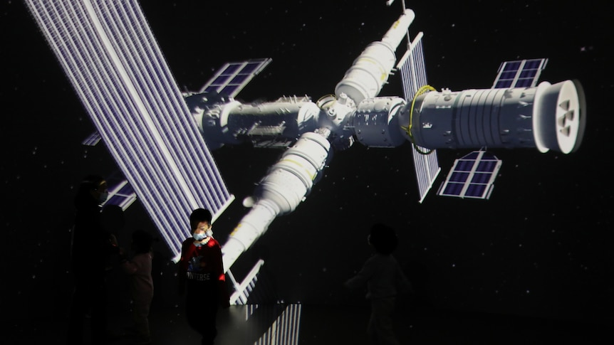 A giant screen shows images of China's Tianhe space station at an exhibition.