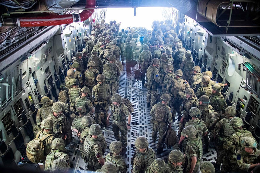 A large group of soldiers in camoflague fatigues and helmets stand ready to walk out of the back of a large aircraft.
