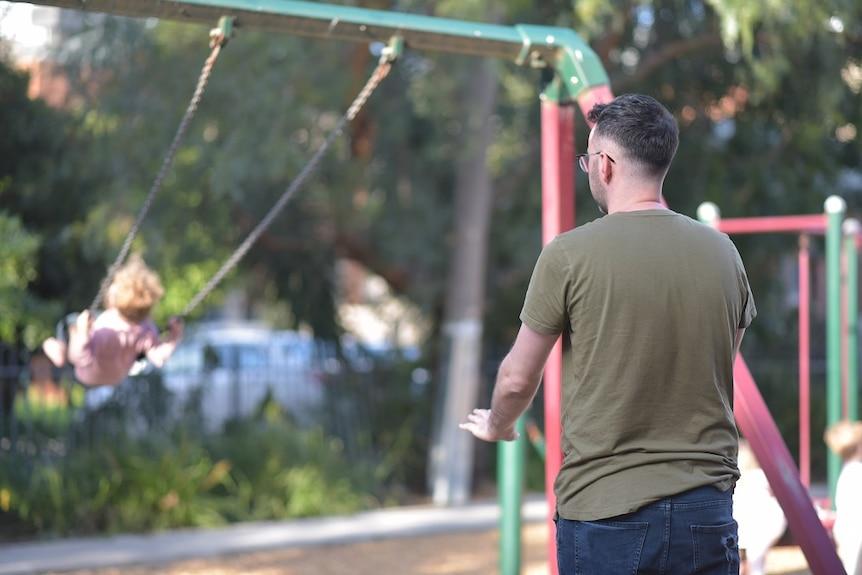 Patrick McIvor pushing child on a swing