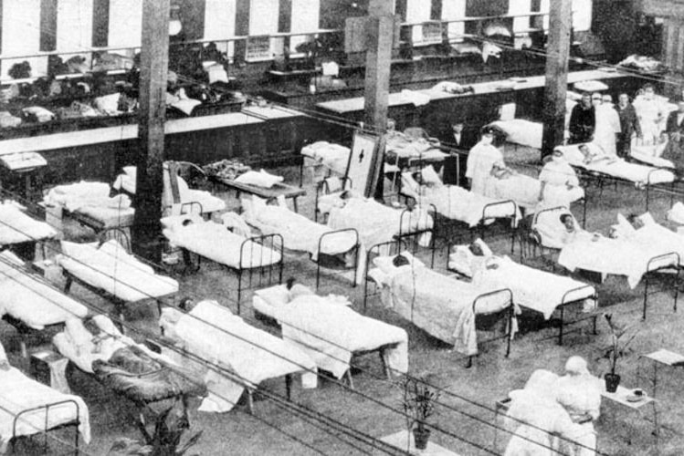A black and white image of a makeshift hospital in a large hall.