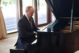 Russian President VladimirPutin looks at the keys as he plays a piano.