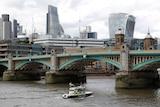 A police boat heads under Southwark Bridge on the River Thames towards London Bridge.