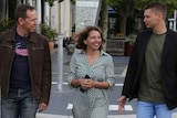 Three Greens members cross the street.