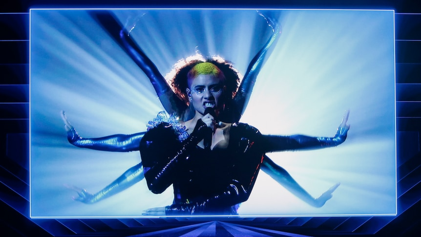 An Australian performer, Montaigne, performs at Eurovision via video, singing while flanked by backing dancers.