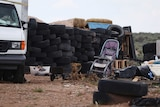 Debris including a baby stroller are seen outside the location where people camped.