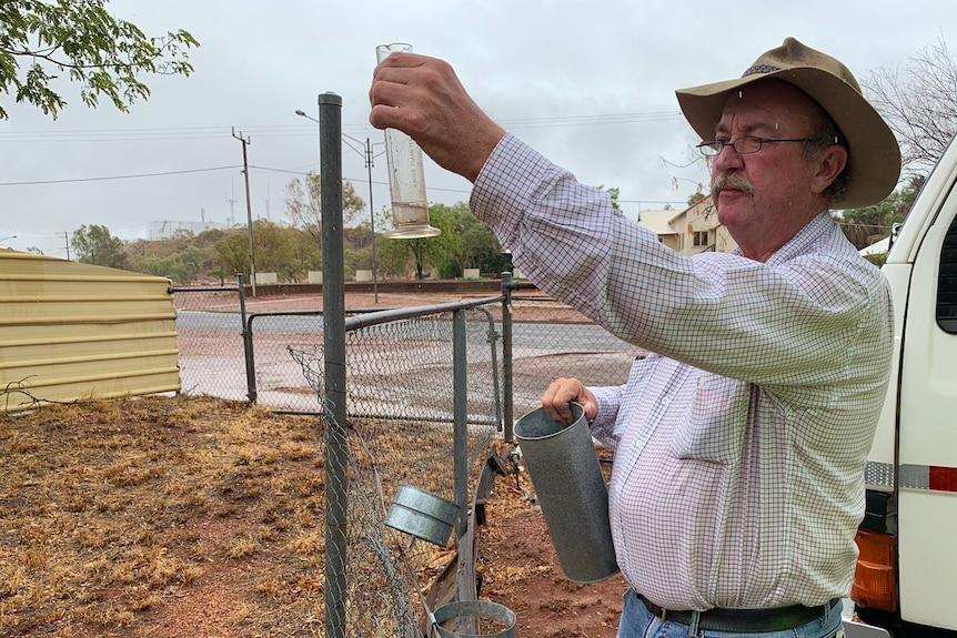 Mike Nash peers at his rain gauge
