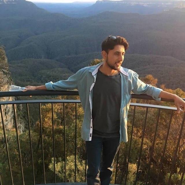 Zeeshan Akbar standing at a lookout near mountain ranges.