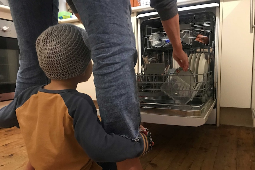 A person unpacks a dishwasher while a child hangs onto their leg for a story on parents feeling 'touched-out'.
