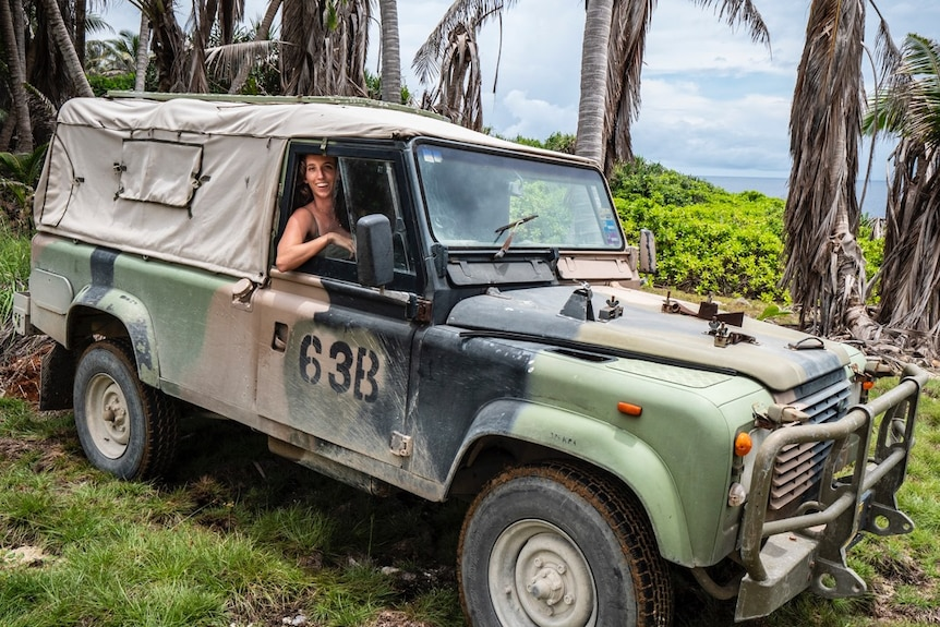 A woman pictured smiling in a camouflage truck in a tropical island looking forest setting.