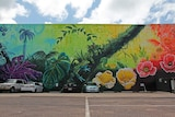 A photo of a brightly coloured tropical mural adjacent to a car park.
