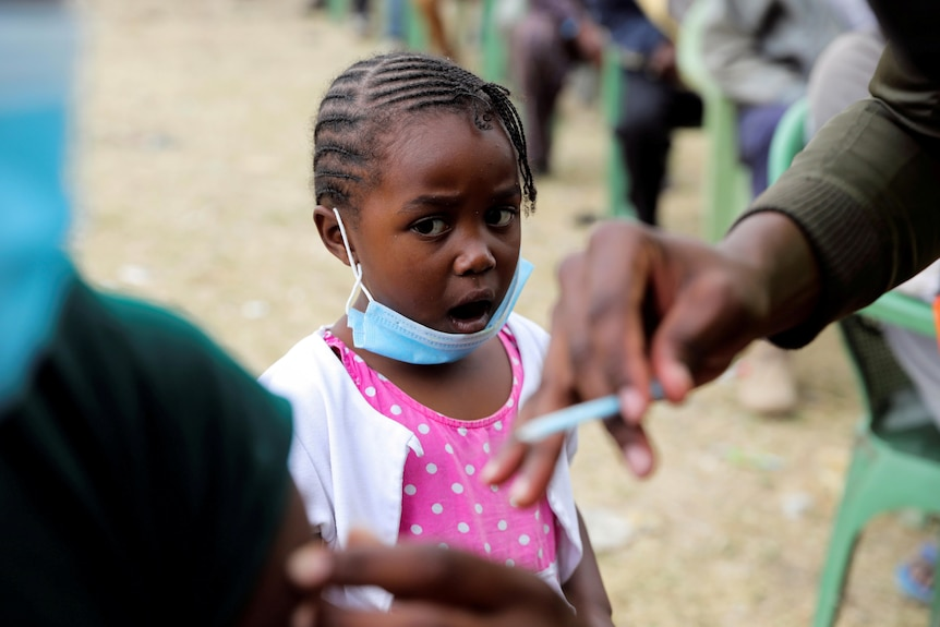 A little girl with a face mask pulled down stares with her mouth agape as a nurse holds a needle to a man's shoulder