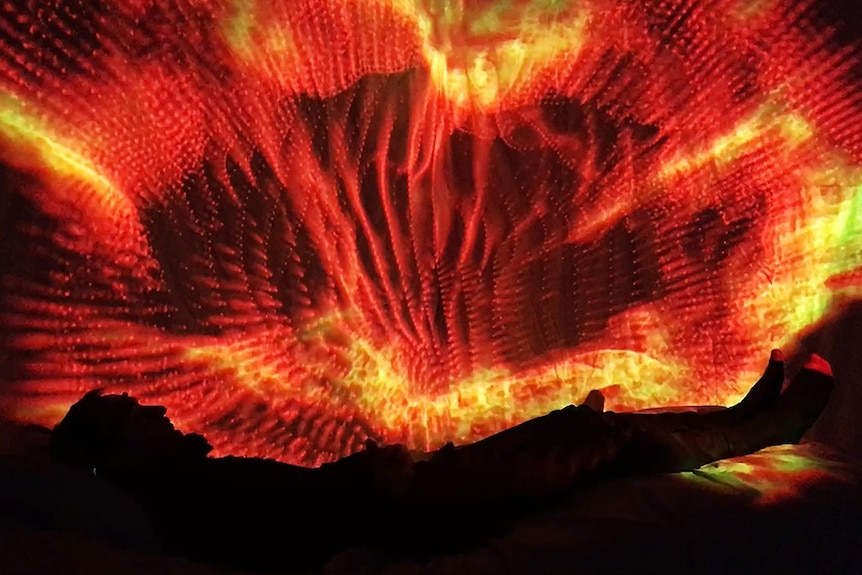 Participant lies in interactive bed wearing VR headset, surrounded by kaleidoscopic visuals.