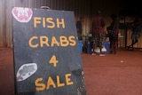 People are buying fish from a market, and there's a sign out the front.