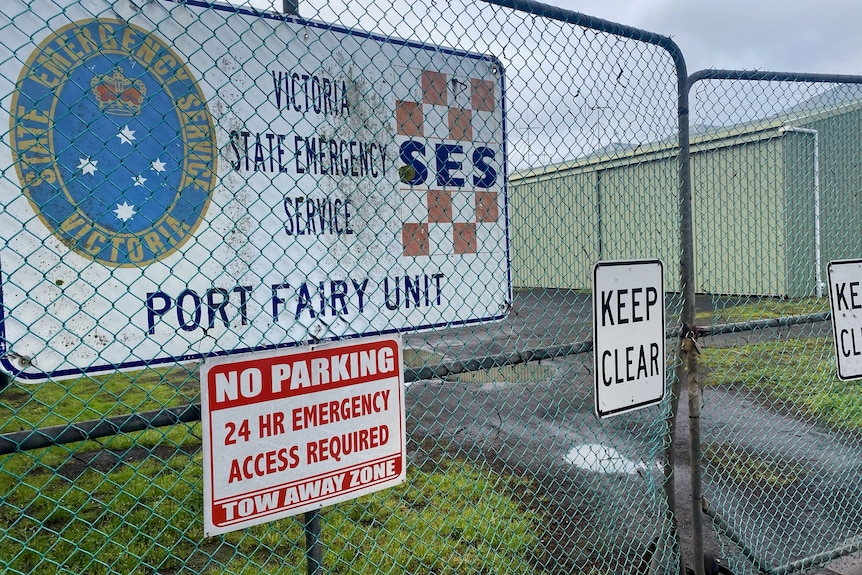 A padlocked gate in front of large sheds, with an SES sign on the fence.