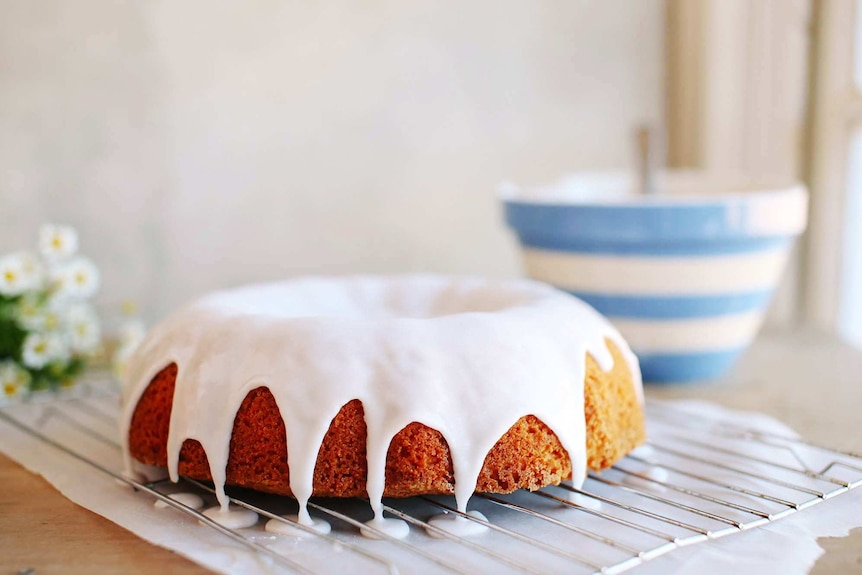 A bundt cake with fresh icing sits on top of a baking rack with a mixing bowl in the background.