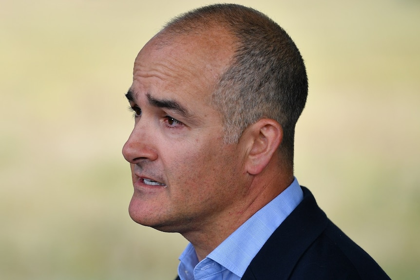 James Merlino, wearing a blue shirt and black jacket, speaks at an outdoors press conference.