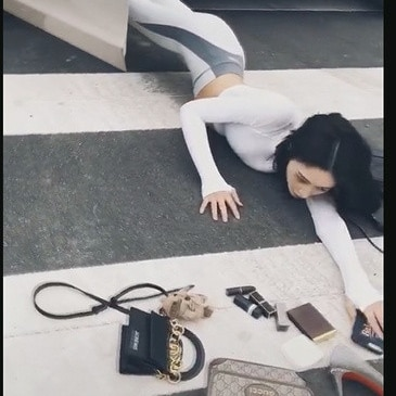 A Chinese influencer posed as she fell out of a car on the crosswalk with her luxury goods scattered on the floor.
