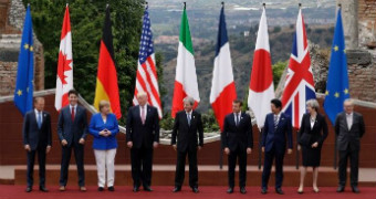 World leaders stand in a line in front of their relevant flags