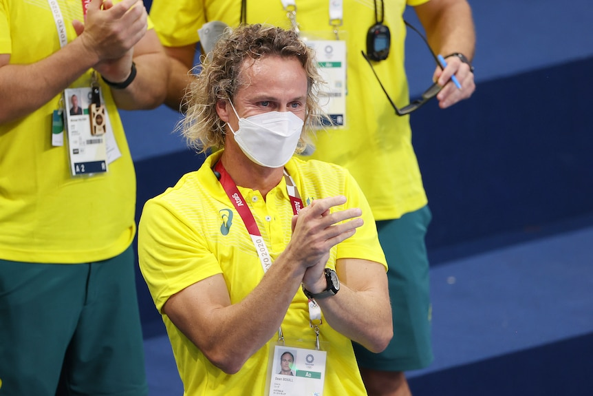 A blonde man wearing a yellow shirt claps his hands