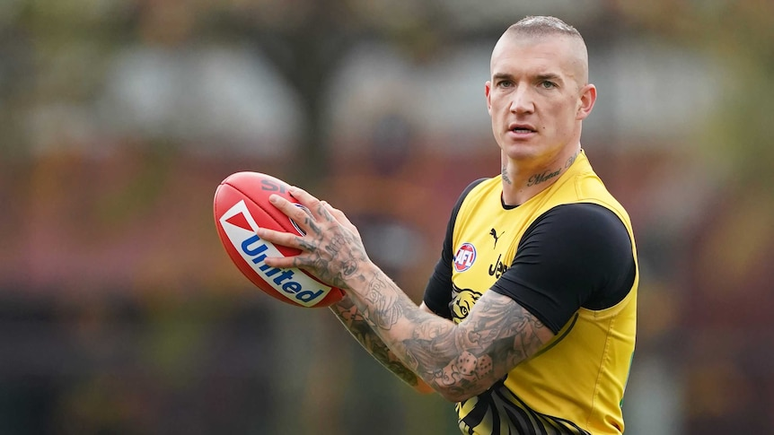 An AFL player holds the ball in front of him as he looks downfield after taking a mark at training.