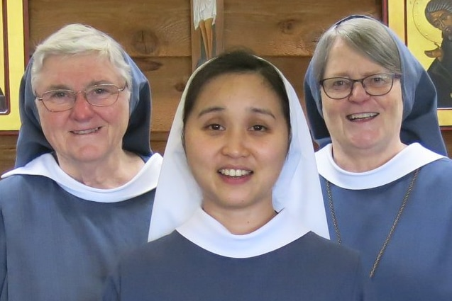 Five women stand close together smiling. All wear long blue robes and white or blue head coverings.