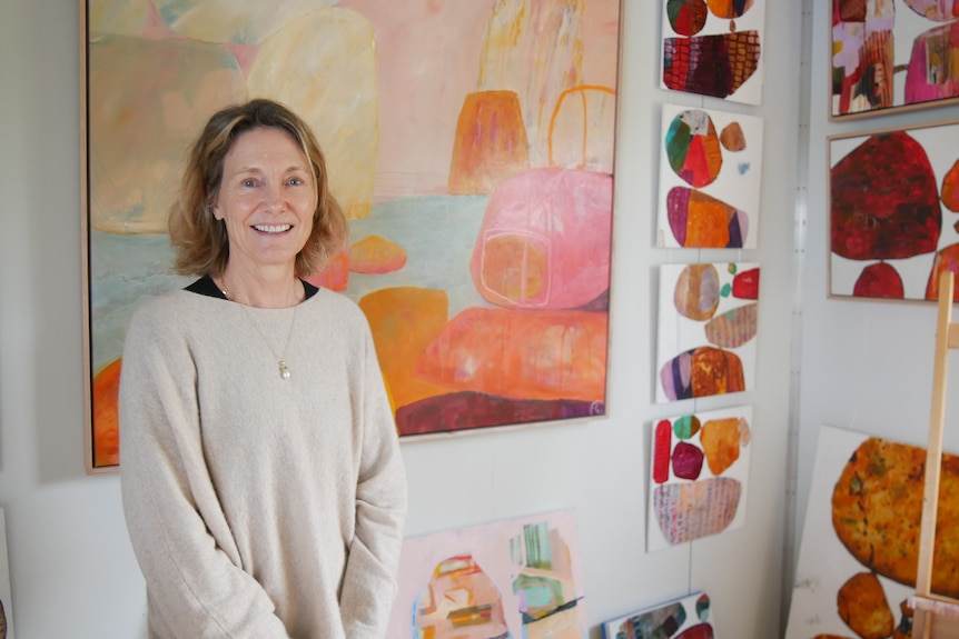 A woman stands in a bright room in front of colourful paintings