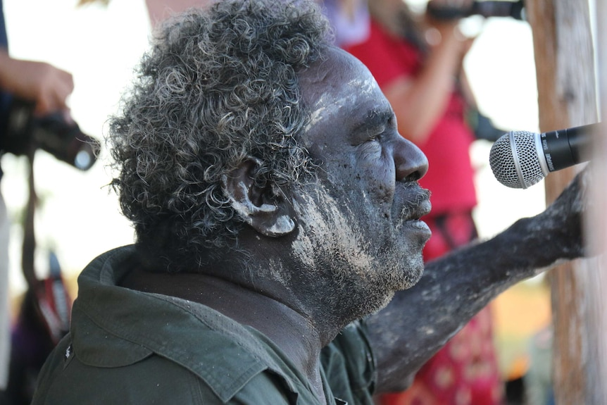 A close-up of Aboriginal man Michael Mungala painted with white mud and singing into a microphone.