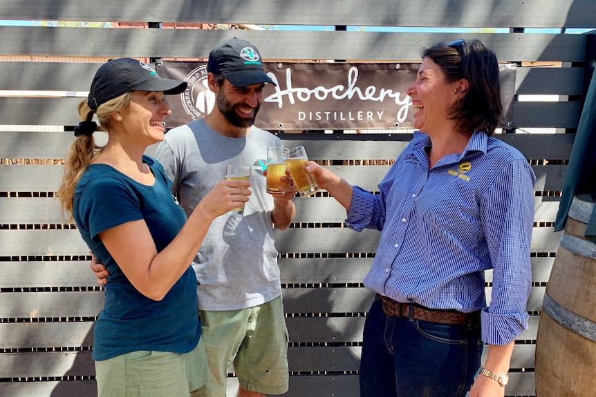 Two women and a man share a laugh as they clink their glasses of beer in a toast, in front of a sign that says Hoochery.