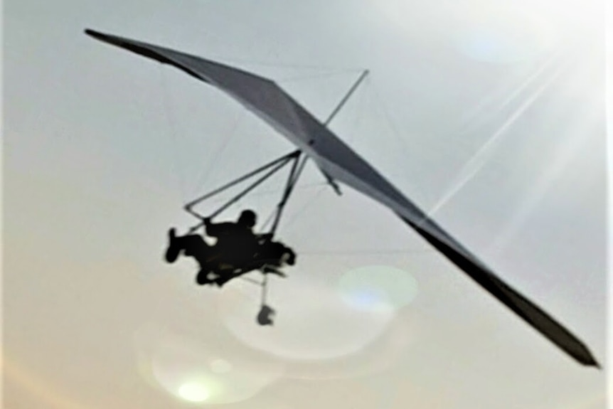 An ultralight plane which looks like a hang glider with a seat at the bottom.