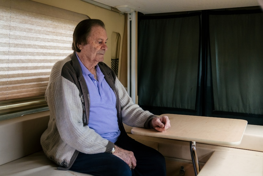A man sits at a table inside a campervan looking downwards.