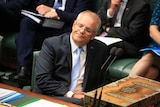 Scott Morrison leans back in his chair with a serious expression on his face