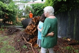 Woman hugs another woman standing in front of fallen tree trunk.