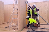 Tradesman work on the timber apartment.