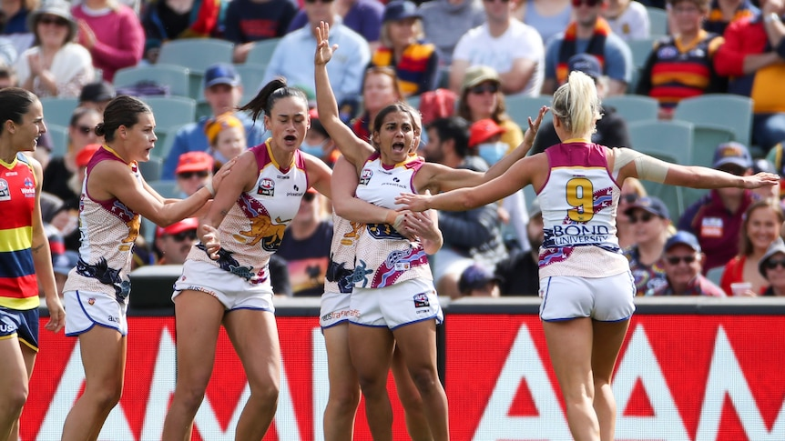 Brisbane players celebrate a goal on the AFL field